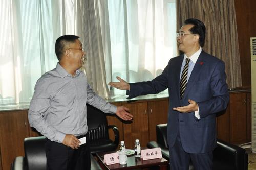 左:杰出校友、蓝光投资控股集团董事局主席杨铿先生;右:校长助理、商学院院长徐玖平教授